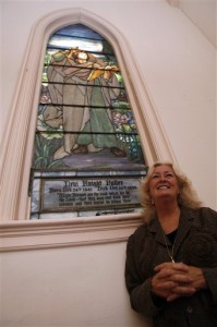 Rev. Suzanne Andrews stands under Tiffany window of St. John the Divine