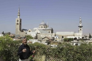 Jacques Montlucon on his rooftop with the Umayyad Mosque in the background