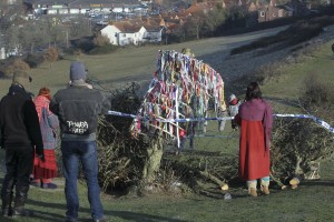 People gather in front of the remains of the Glastonbury Holy Thorn tree
