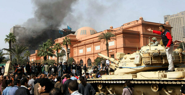 Protesters outside Cairo museum, NDP building burning next to it