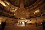 Restorers at work in the audience hall of Bolshoi, giant chandelier and sconces wrapped in protective plastic