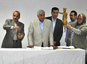 Zahi Hawass (center) and staffers holding recovered King Tut statue (right) and fan (left)