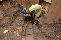 Archaeologist excavating the inner wall of The Curtain Theatre yard