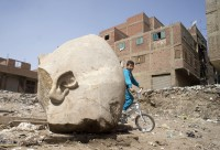 Boy bikes past colossal head. Photo by Amr Nabi/AP.
