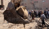 Head scooped up by bulldozer. Photo by Khaled Elfiqi/European Pressphoto Agency.