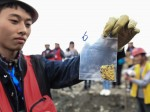 Member of excavation team holds gold artifact recovered from site. Photo by Chen Xie, Xinhua News Agency.