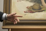 FBI Special Agent Jacob Archer points to pool cue damage on recovered Norman Rockwell painting. Photo by Matt Rourke/AP.