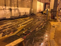 Ship timbers kept wet on tarps in the bus barn. Photo copyright Scripps Media.