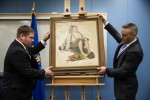 FBI Special Agents Don Asper, left, and Jacob Archer displays a recovered Norman Rockwell painting. Photo by Matt Rourke, AP.