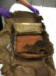 Brown parcel paper opened to reveal shroud. Copyright National Museums Scotland.