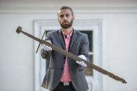 Museum director Bartłomiej Bartecki holding the 14th century sword found in Mircze. Photo by Wojciech Pacewicz/PAP.
