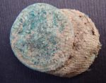 Coin stack with textile fragments still attached by corrosion. Photo courtesy the Somerset County Council.