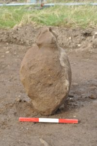 Carved stone recovered before cleaning. Photo courtesy ORCA Archaeology.
